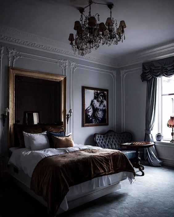 a refined moody bedroom with a statement mirror in a simple frame and a chic chandelier that make the space wow