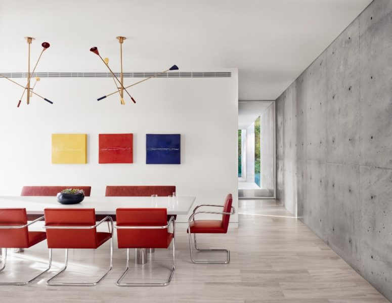 Bright red chairs and a colorful gallery wall spruce up the neutral dining room with a concrete accent wall