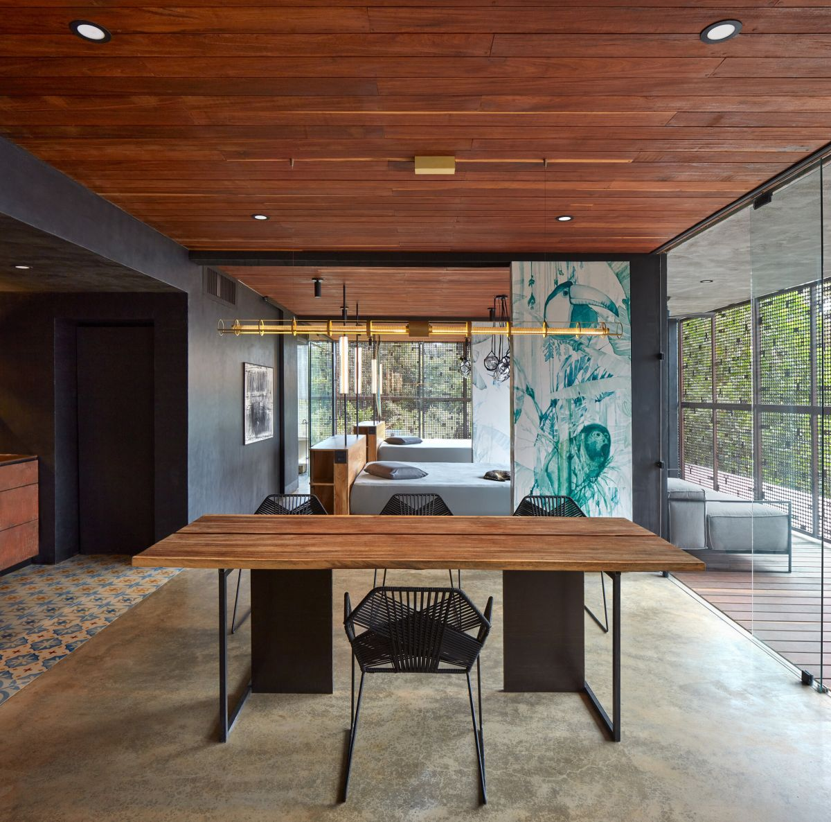 The dining space is done with black chairs and a simple wooden dining table