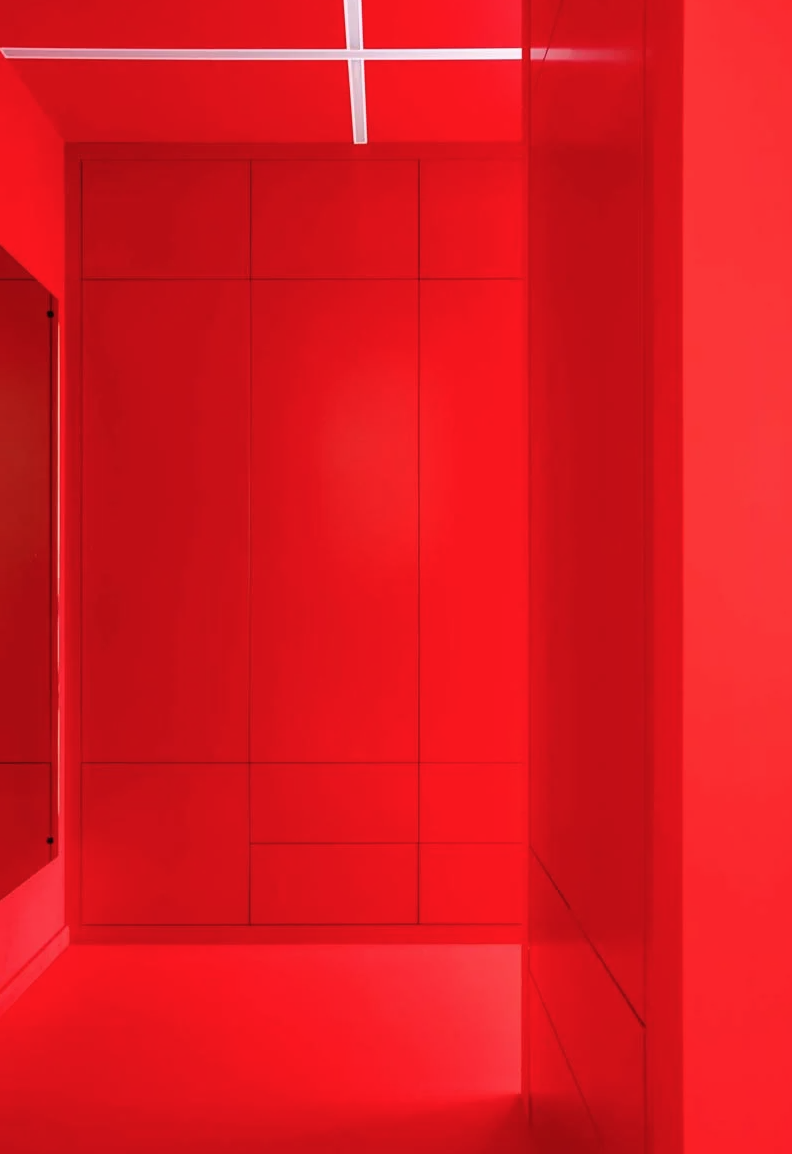 The entryway is bright red, with sleek storage units and a large mirror and built in lights