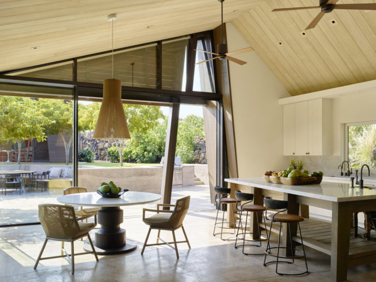 The kitchen is all-neutral, and there's a small dining zone with a wooden pendant lamp