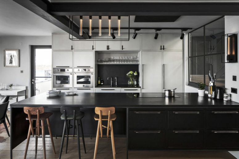 The kitchen is black and white, with plywood and metal cabinets, with a catchy lamp and tall stools
