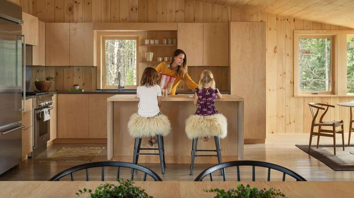 The kitchen is made of light colored plywood, with a window to fill it with light