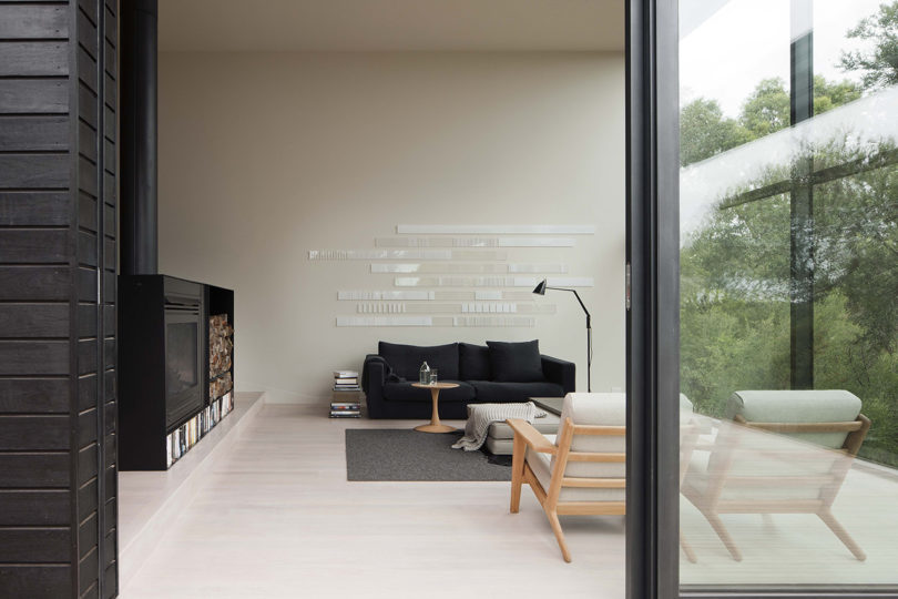 The living room is done with a large hearth, firewood, a black sofa and a cool minimal wall art