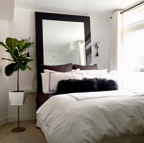a small neutral bedroom with a modern statement mirror in a dark frame that catches an eye and makes the space cool