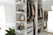 05 a small open closet in white with shelves, holders and drawers doubles as a space divider