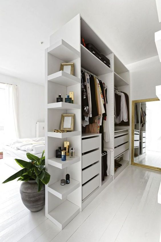 a small open closet in white with shelves, holders and drawers doubles as a space divider