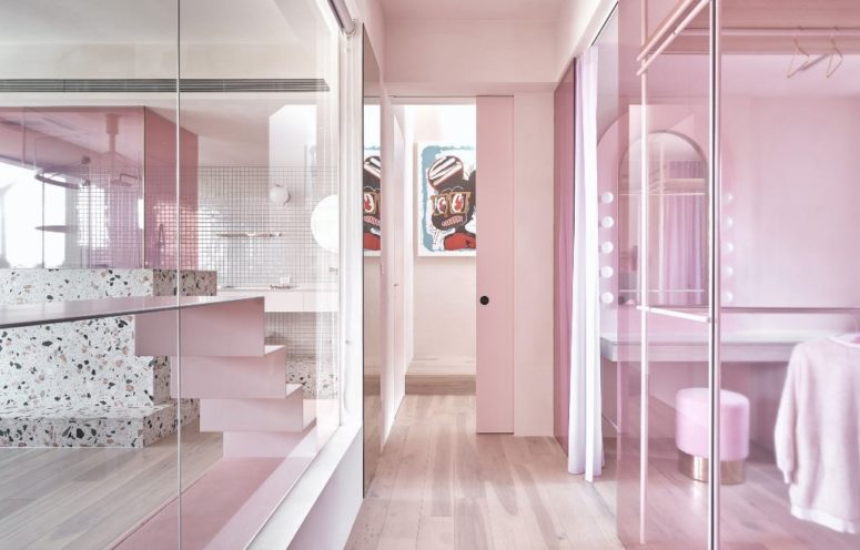 Some spaces are divided only with glass partitions in pink to connect them and brign more light here