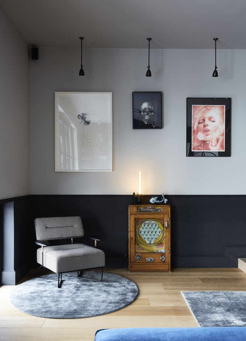 This nook features a unique gallery wall, pendant lamps, a little side table and a chic mid century modern chair