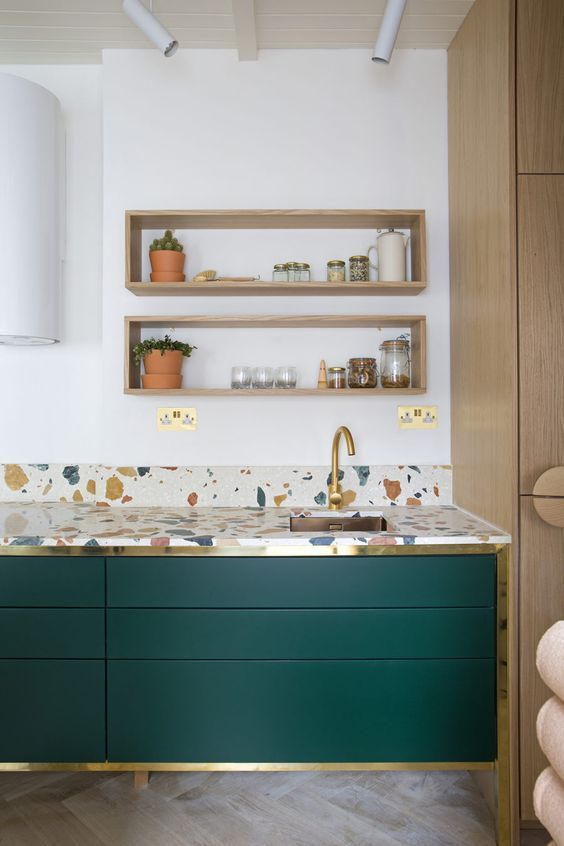 hunter green kitchen cabinets accented with gold touches and with bright terrazzo countertops are very chic and bold