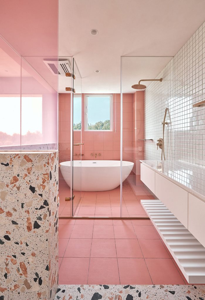 The bathroom also features lots of pink, neutral tiles and terrazzo