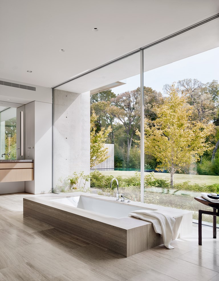 The bathroom features a built-in tub placed next to a glass wall to enjoy the views