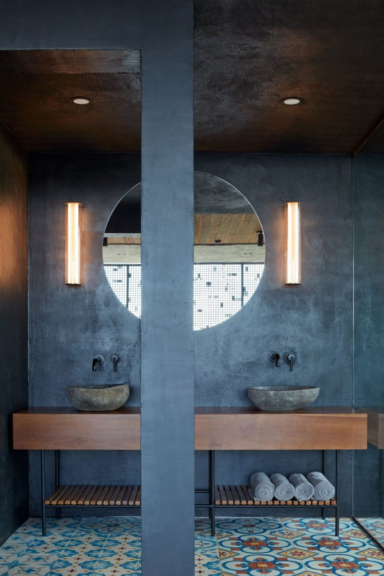 The master bathroom shows off concrete walls, cool  colorful tile floors, and rough stone sinks