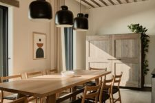07 This is an indoor dining space with cool black lamps, black chairs, wooden furniture and black chairs