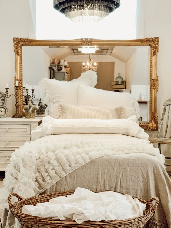 a gorgeous statement mirror in a refined gold frame is a nice alternative to a headboard that will enlarge the space