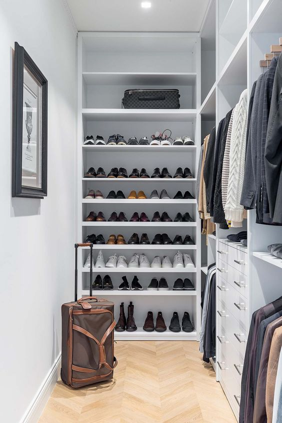 a small and stylish manly closet in white, with lots of open shoe shelves, holders with hangers, built-in drawers and lights