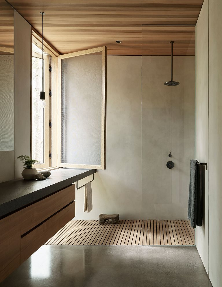 The bathroom is done with concrete and sleek wood, with dark fixtures and a window for a view