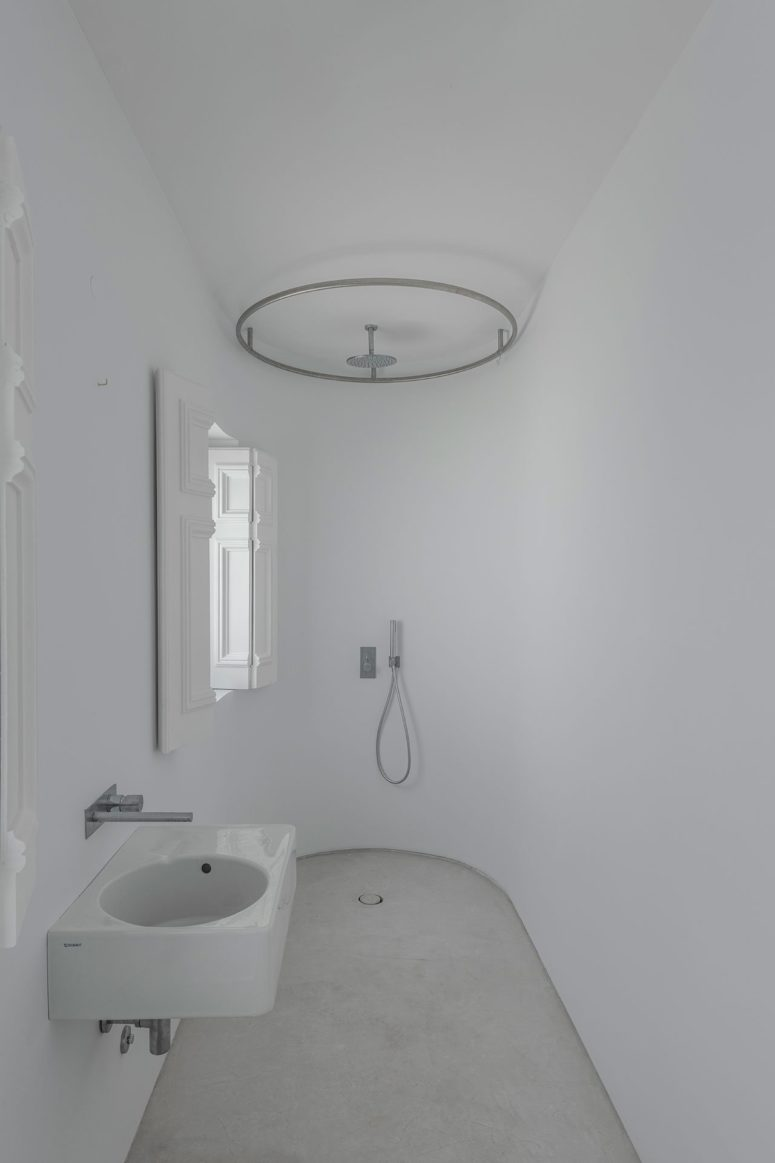 The bathroom is pure white, with a small shower space and a wall-mounted sink, the original shutters preserved