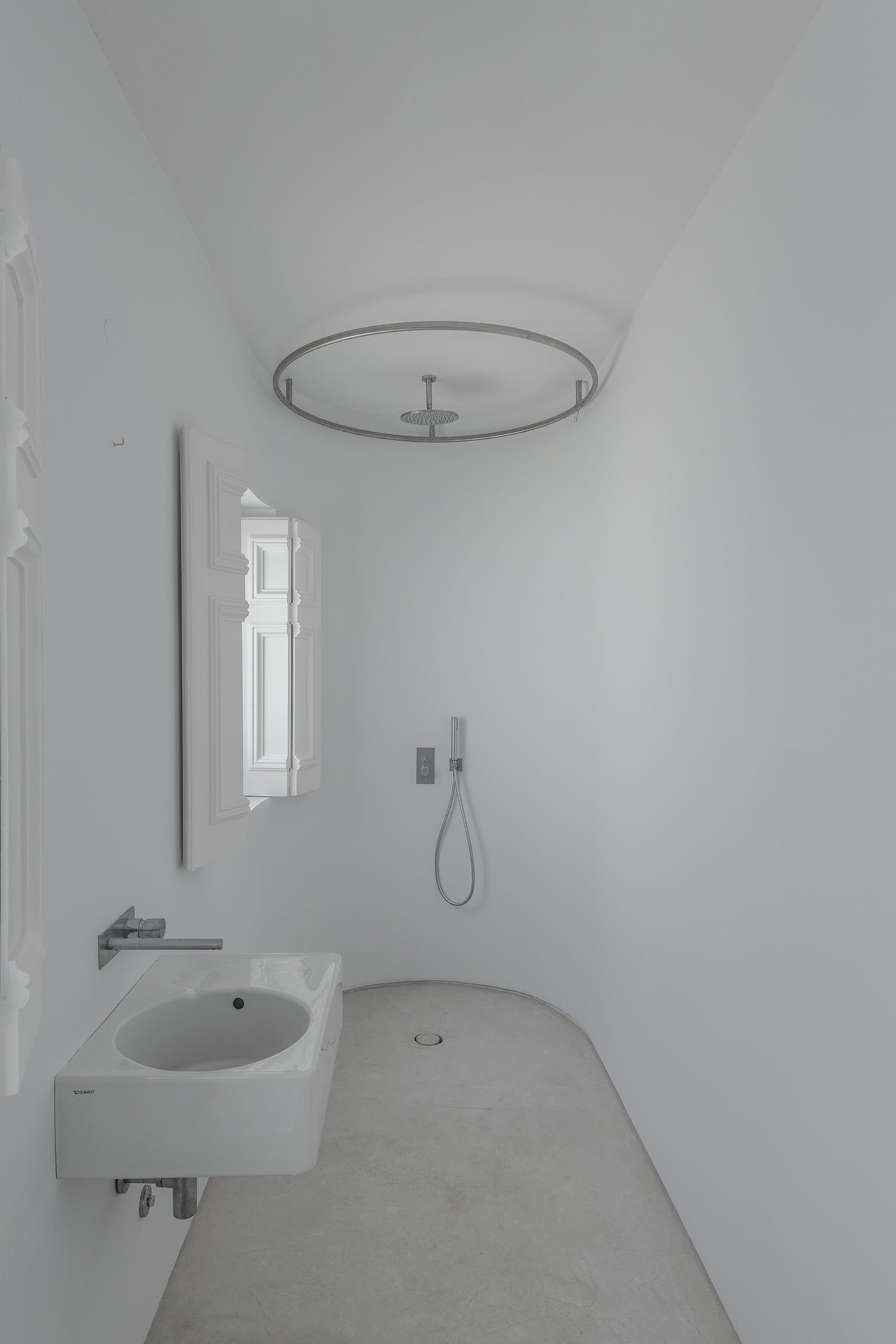 The bathroom is pure white, with a small shower space and a wall mounted sink, the original shutters preserved