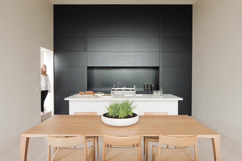 The kitchen is done in black, with sleek cabinets and everything hidden, the kitchen island is white, and the dining space is also here