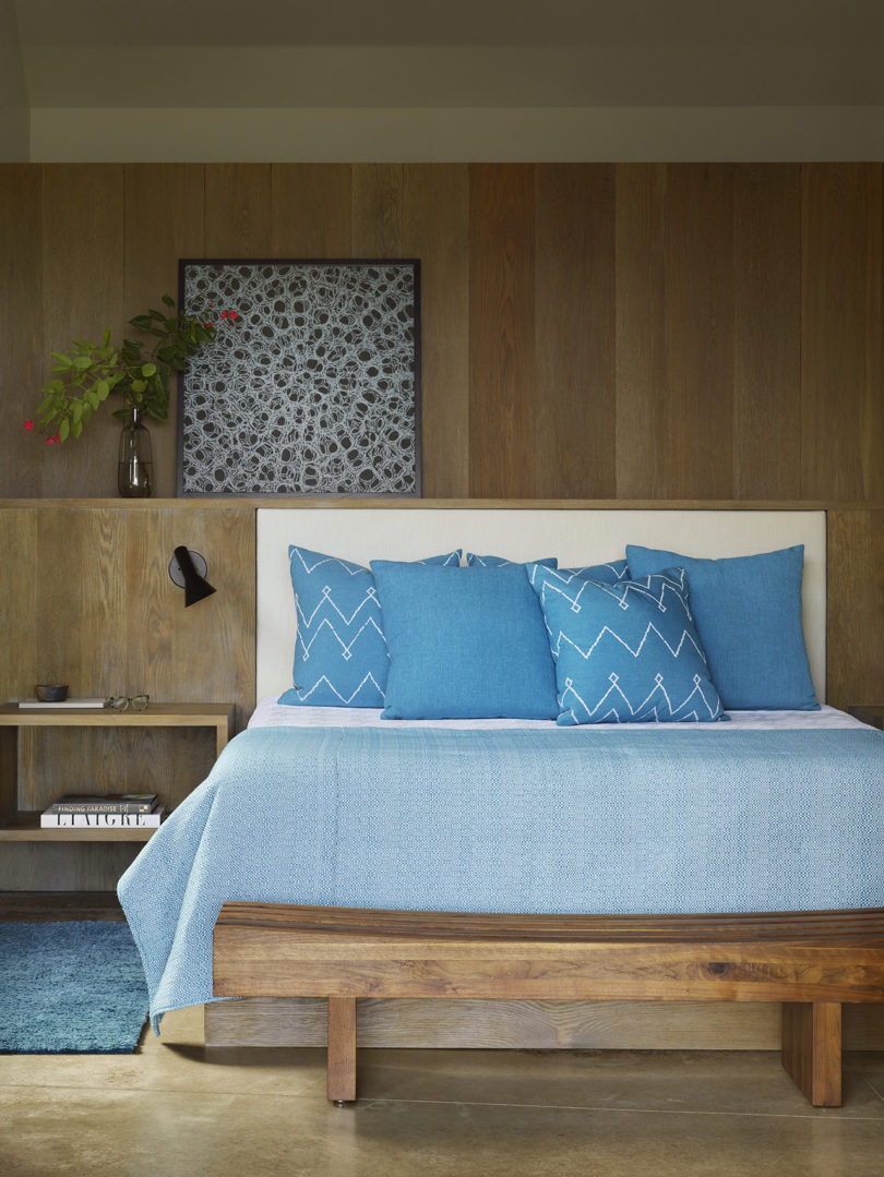 The master bedroom is done with a lot of natural wood, with a built in bed and a bench, with a pretty artwork
