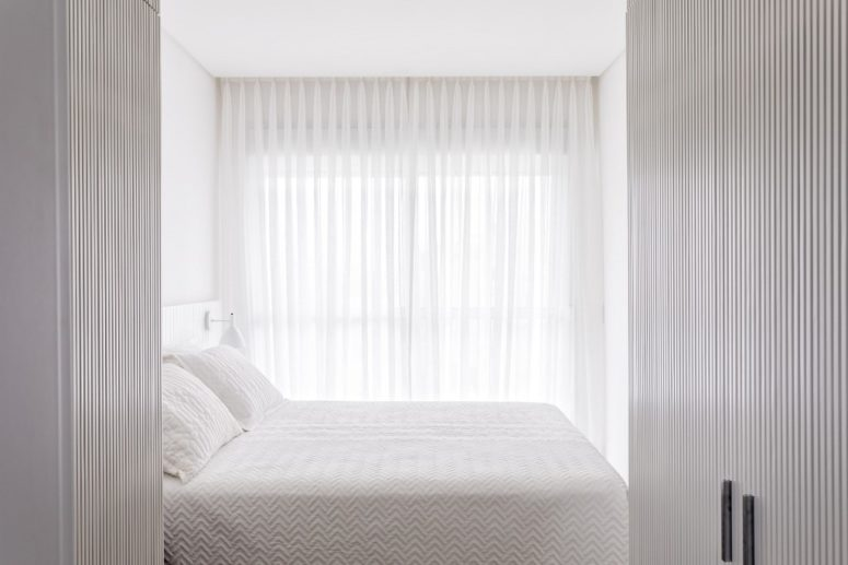 The master bedroom is pure white and rather small, there's some furniture and a gorgeous view