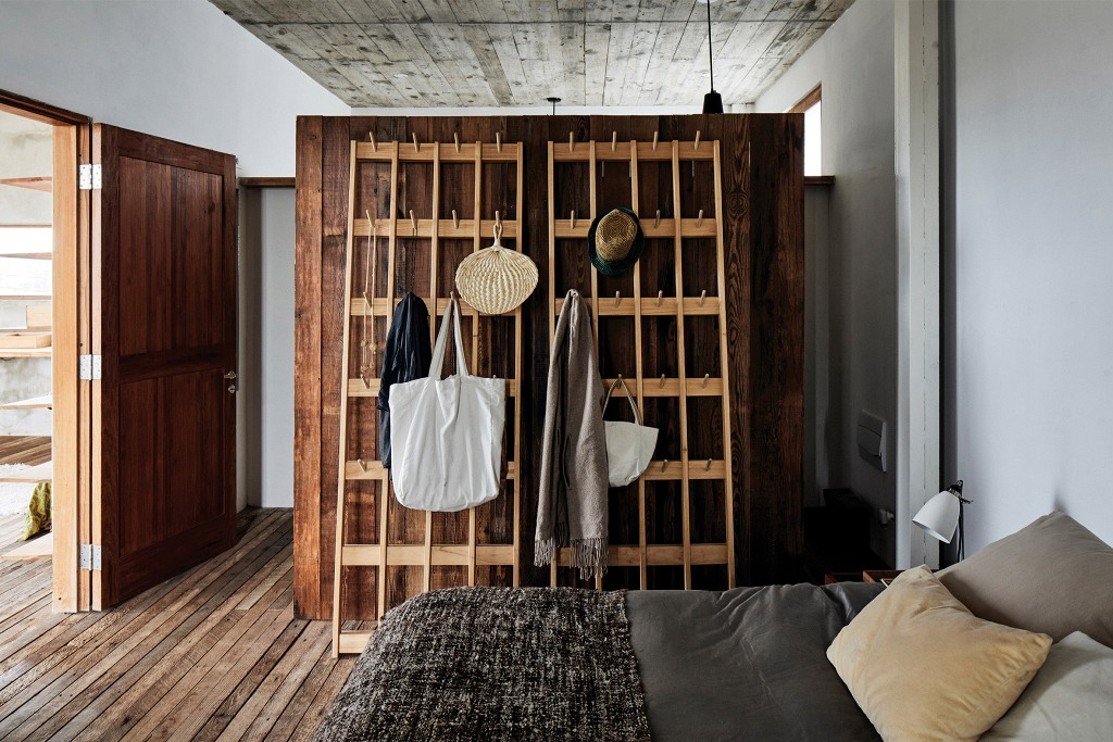 The master bedroom shows off a large wood clad closet and a comfy bed with lots of pillows
