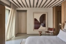 08 The master bedroom shows off wooden panels, a comfy bed, sconces and a statement artwork