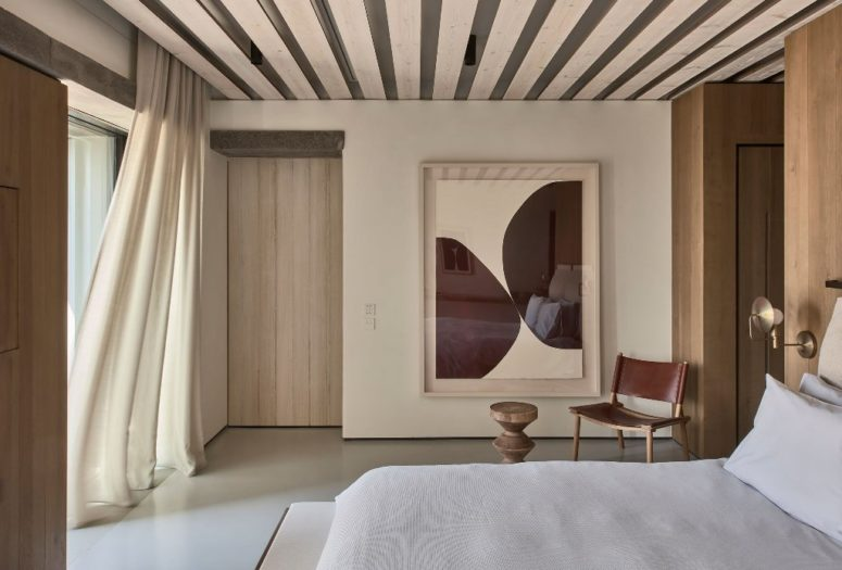The master bedroom shows off wooden panels, a comfy bed, sconces and a statement artwork
