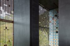 08 The shower spaces are done with the same bright tiles and there are perforated metal screens