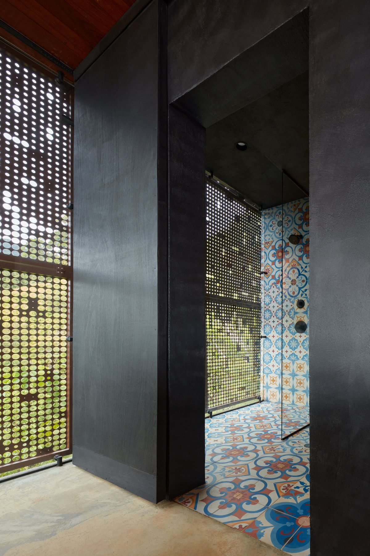 The shower spaces are done with the same bright tiles and there are perforated metal screens