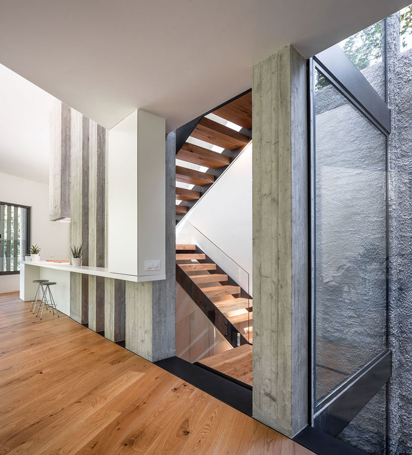 The staircase space features glass walls to fill the space with light and make it more airy