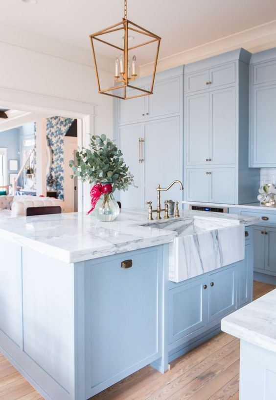a beautiful and elegant light blue kitchen with white marble countertops that make a luxurious statement accenting the colors