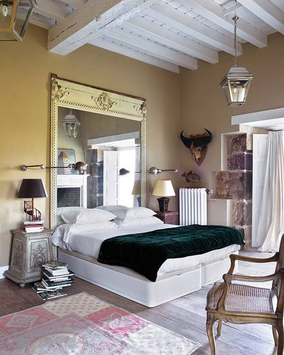 an eclectic bedroom with an oversized mirror in a vintage frame and some shabby chic furniture that make the space refined