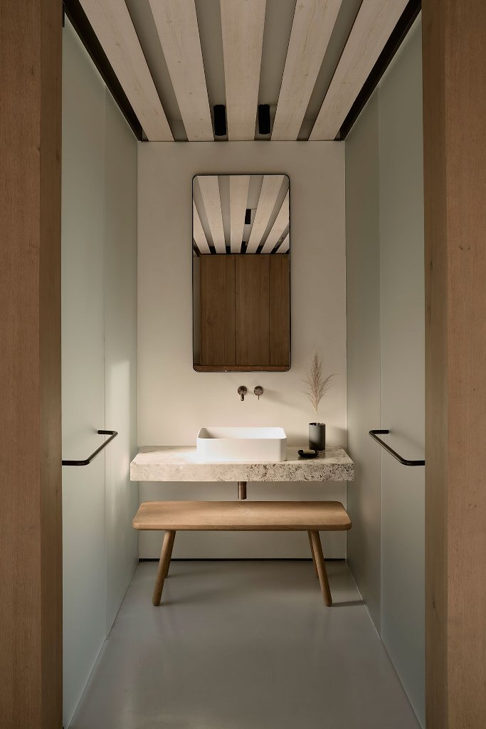 The bathroom is minimalist, with a stone vanity, wooden bench and frosted glass clad showers