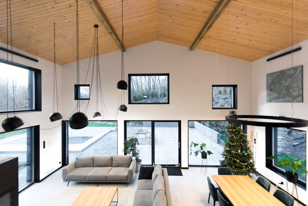 The double height living area is framed by lots of irregular windows which bring in sunlight and beautiful views