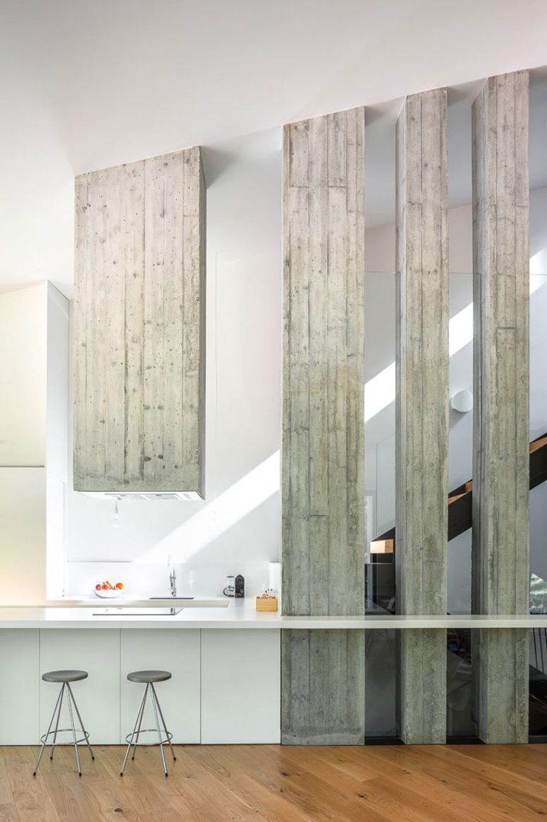 The kitchen is minimalist, with sleek cabinets, there's a whitewashed wooden hood and some beams