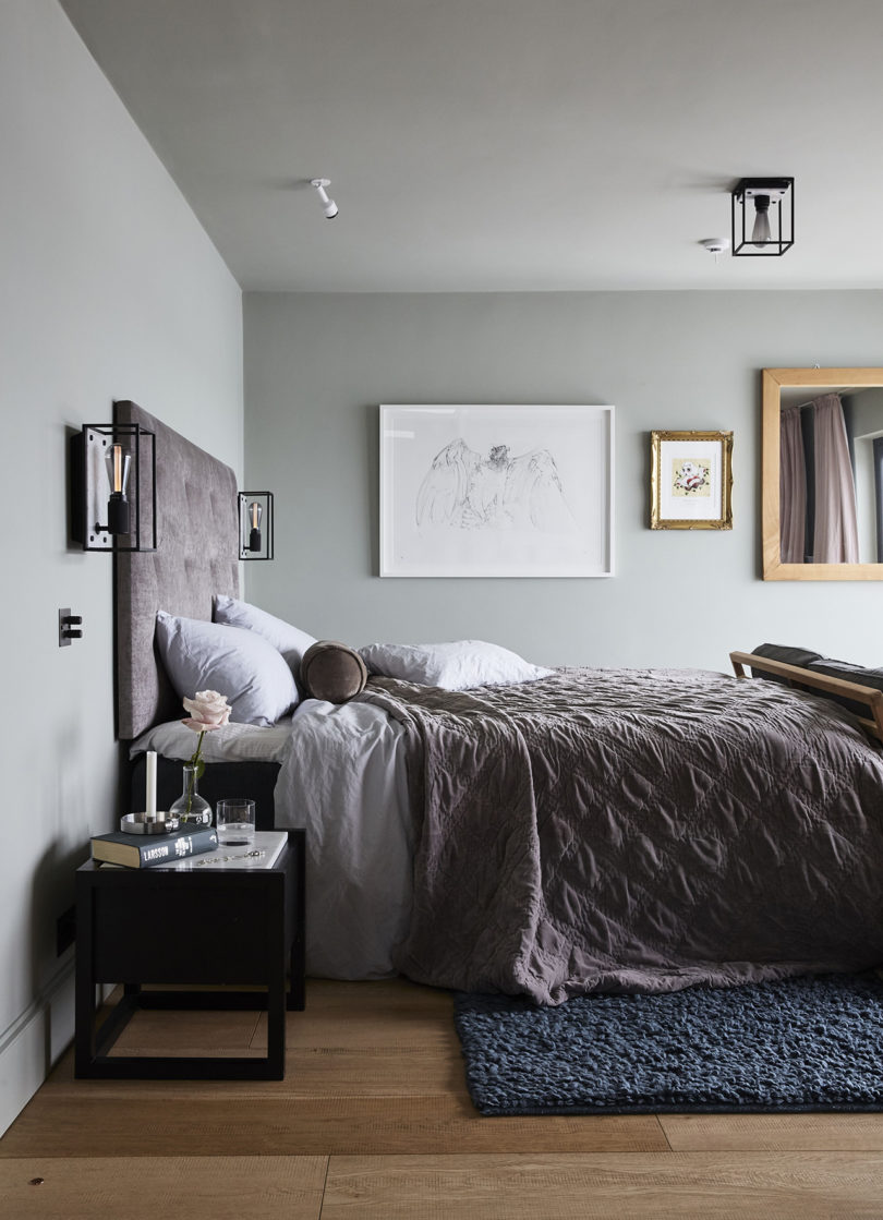 The master bedroom is very soothing, with grey walls, a gallery wall, dusty pink textiles and touches of black