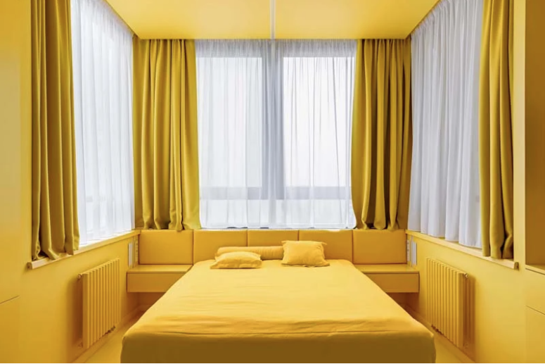 There are several windows to maximize the light, a bed, an upholstered storage headboard and a storage unit