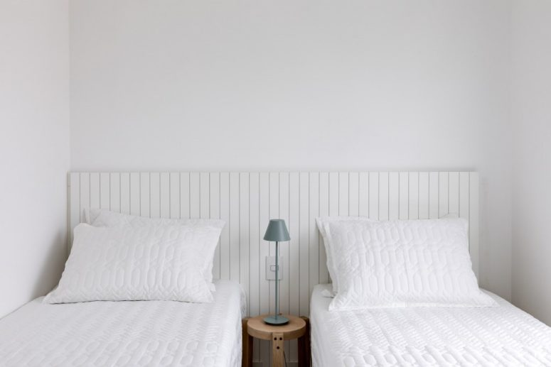 There's also a twin guest bedroom done in white, with two comfy beds and a tiny nightstand between them