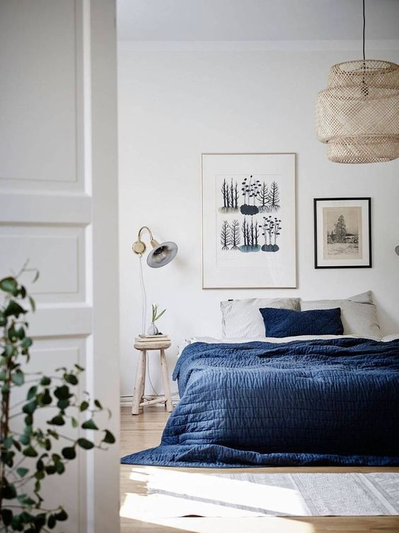 a gallery wall with various artworks is a cool idea for a contemporary bedroom, who needs a headboard