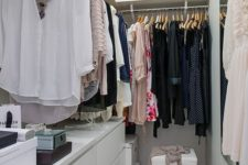 09 a small contemporary closet in white, with a large open shelf with boxes, dressers, holders with hangers and a stool