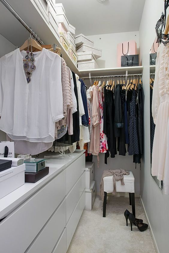 a small contemporary closet in white, with a large open shelf with boxes, dressers, holders with hangers and a stool