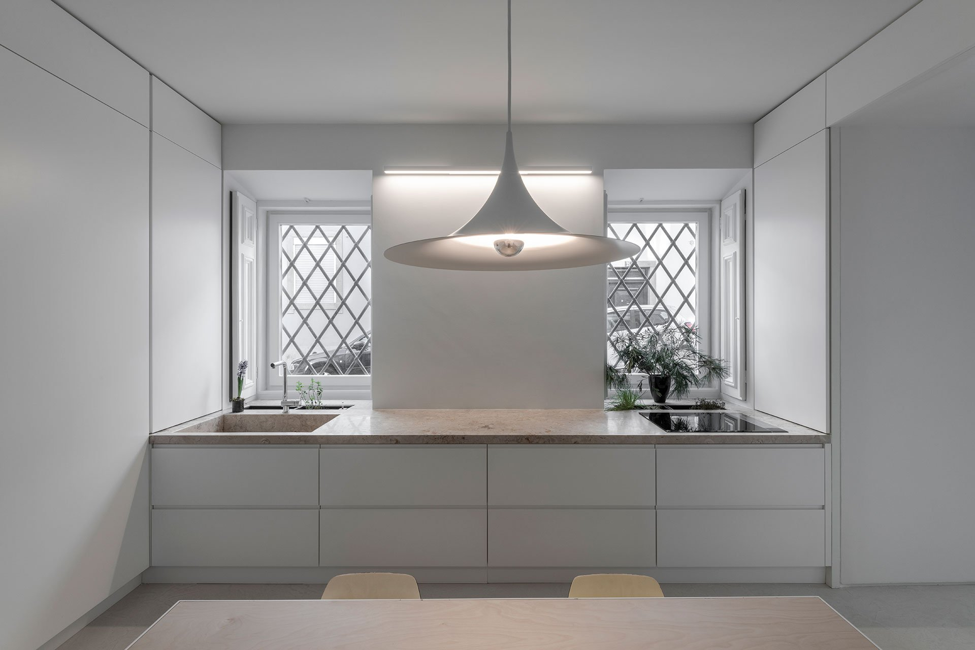 The kitchen is pure white, with sleekcabinets, a stone countertop, a cool pendant lamp