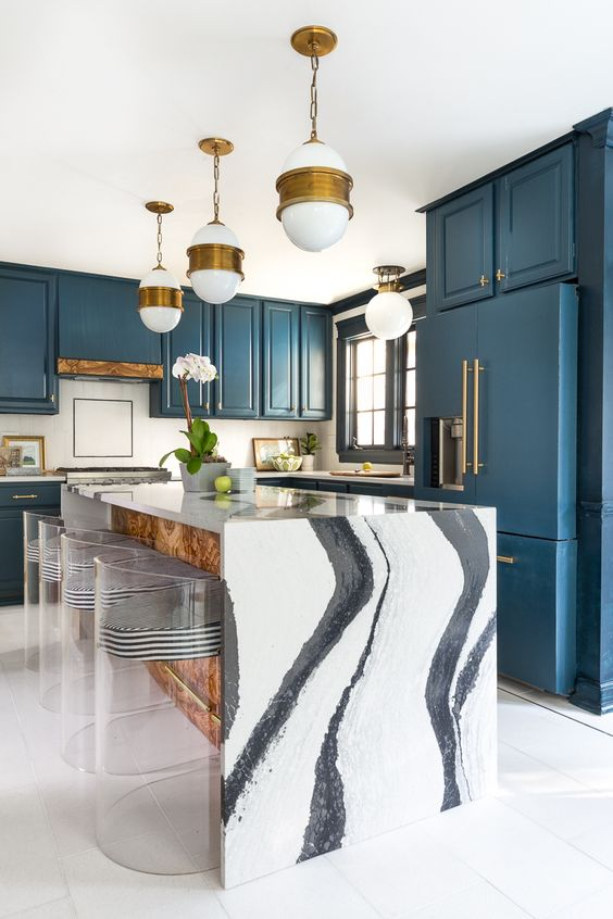 a chic blue kitchen and a kitchen island with a gorgeous white marble waterfall countertop that makes a statement here