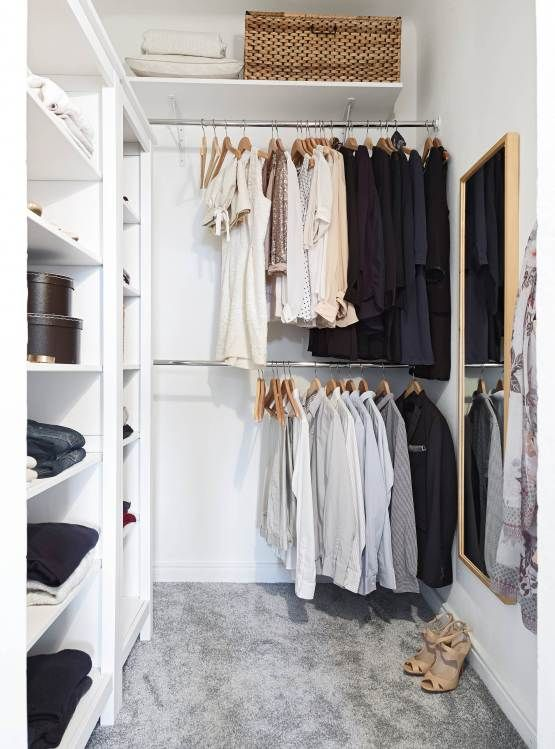 a small contemporary closet with holders for hangers, open shelves for various stuff, a basket and a large mirror