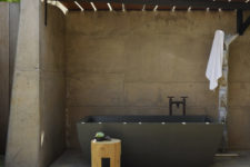 11 There's an outdoor bathroom designed of concrete and with a large stone tub