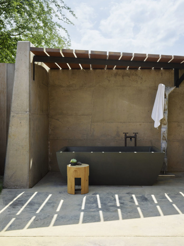 There's an outdoor bathroom designed of concrete and with a large stone tub