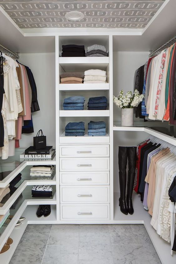 a small contemporary closet with open shelves, drawers, holders for hangers, glass shelves and a wallpaper ceiling
