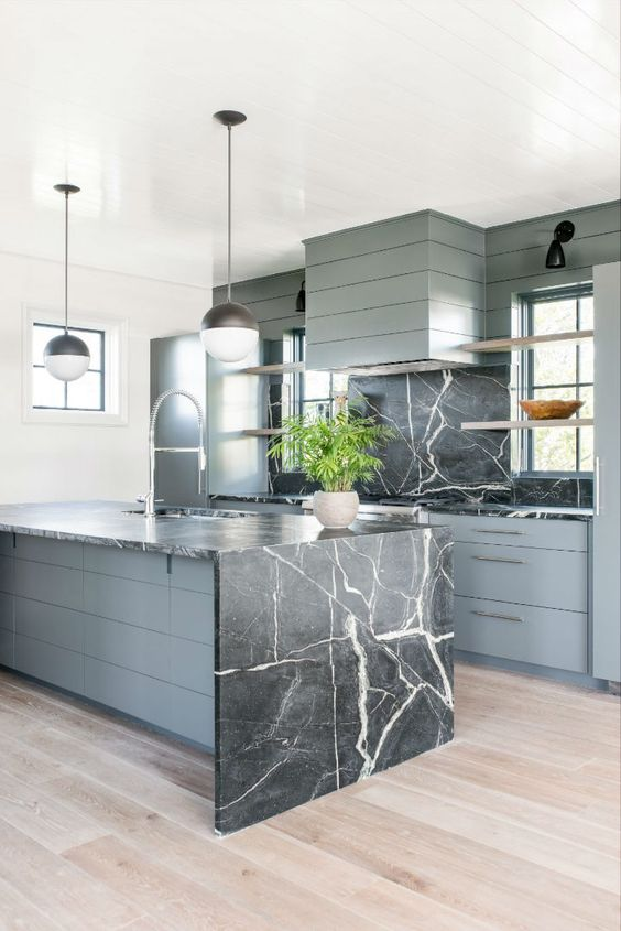 a grey wooden kitchen with a black marble backsplash and a matching island with a waterfall countertop